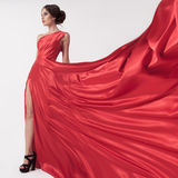 Young beauty woman in fluttering red dress. White background. Stock Photography