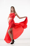 Young beauty woman in fluttering red dress Stock Photos