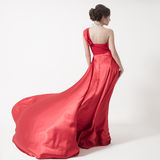Young beauty woman in fluttering red dress. White background. Stock Images