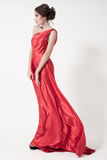 Young beauty woman in fluttering red dress. White background. Royalty Free Stock Image