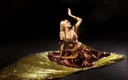 Young beauty woman lay on gold saber Stock Images