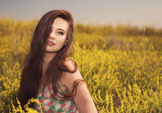 Young beauty woman in the park with yellow flowers photo Stock Images