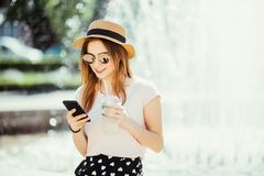 Young beauty woman with phone chating or surf in internet drinks mojito fruit cocktail against fountain in the street. Young summer beauty woman with phone stock photo