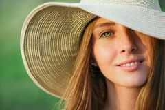 Young beauty woman in summer hat. Over green background. Half face shot Royalty Free Stock Photo