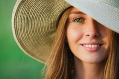 Young beauty woman in summer hat. Over green background. Half face shot Royalty Free Stock Photography