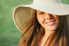 Young beauty woman in summer hat. Over green background. Half face shot Royalty Free Stock Images