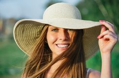 Young beauty woman in summer hat. Young  smiling beauty woman in summer hat over green background. Half face shot Royalty Free Stock Photography