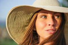 Young beauty woman in summer hat. Young  smiling beauty woman in summer hat over green background. Half face shot. Model looking at the side Stock Photo