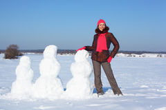 Young beauty woman and three snowmans Royalty Free Stock Photography