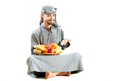 Young bedouin. Man in traditional dress with fruit Royalty Free Stock Photography