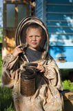 Young beekeeper boy using a smoker on bee yard Stock Photos