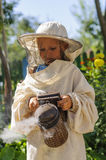 Young beekeeper boy using a smoker on bee yard Stock Images