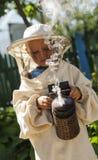 Young beekeeper boy using a smoker on bee yard Royalty Free Stock Photo