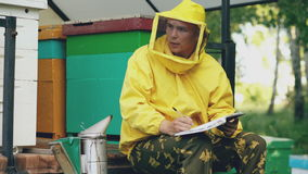 Young beekeeper man write in notepad checking harvest while sitting near beehives stock video