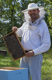 Young beekeeper smiling. And showing his bee colony Stock Photo
