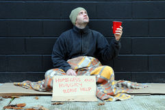Young beggar. Young man sitting on sidewalk in city, begs for change on cold autumn day Stock Photos