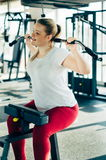 Young beginner girl exercising in the fitness gym, with lat machine Royalty Free Stock Image