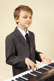 Young beginner musician in suit playing the digital piano Royalty Free Stock Photography