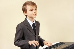 Young beginner musician in a suit playing electronic piano Stock Photography