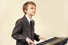 Young beginner musician in suit playing the electronic synth Stock Image
