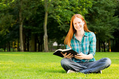 Young Believer with a Bible in a Park. A Christian woman holding a Bible and smiling at the camera, photographed in a public park Stock Photography