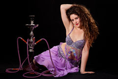 Young belly dancer posing with hookah Stock Photos
