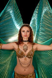 Young belly dancer posing with Isis wings. A young belly dancer poses in an elaborate costume with green translucent Isis wings Royalty Free Stock Photo
