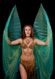 Young belly dancer posing with Isis wings. A young belly dancer poses in an elaborate costume with green translucent Isis wings Stock Photos