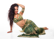 Young belly dancer sitting. A beautiful young belly dancer strikes a seductive pose on the floor Stock Photography