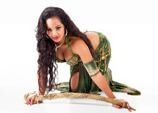 Young belly dancer  with sword. A beautiful young belly dancer poses seductively on the floor with a sword Stock Photography