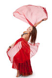 Young belly dancer turning with veil sleeves. A young belly dancer makes a barrel turn with her translucent sleeves spinning out Royalty Free Stock Images