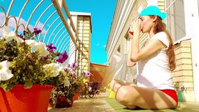 Young beutiful woman drinking tea or coffee on the sunny terrace Stock Image