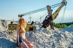 Young bewitching sexy girl with long beautiful hair in denim shorts and a bikini bathing suit sitting on a mountain of sand in the Royalty Free Stock Photos