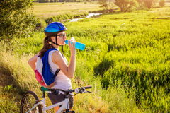 Young bicyclist drinking water by the river Stock Photo