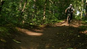 Young bicyclist in full face helmet riding on mountain bicycle on forest offroad. Young bicyclist in full face helmet riding on dh mtb on offroad in summer stock video footage