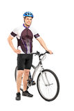Young bicyclist posing next to a bicycle Royalty Free Stock Images