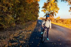 Young bicyclist riding in autumn field at sunset. Happy woman smiling stock photo