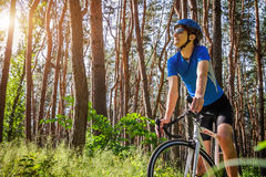Young bicyclist riding in the forest Royalty Free Stock Photography