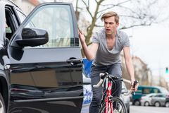 Young bicyclist shouting while swerving for avoiding dangerous collision. Angry young bicyclist shouting while swerving for avoiding dangerous collision with the Royalty Free Stock Images