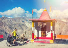 Young bicyclist standing on mountain road near tibeb prayer place, North India, Himalayas Royalty Free Stock Photo
