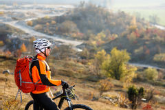 Young bicyclist standing near and looking to mountains Royalty Free Stock Photography