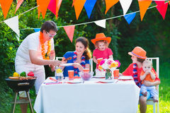 Young big dutch family having grill party. Happy big Dutch family with kids celebrating a national holiday or sport victory having fun at a grill party in a Royalty Free Stock Images