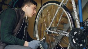 Young bike repairing master is adjusting wheel mechanism with wrench and rotating wheel to check quality of work. Cycle. Young bike repairing master is adjusting stock video