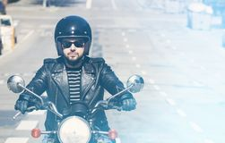 Young biker in a black leather jacket ride a motorcycle on blurred background. Horizontal. Stock Photos