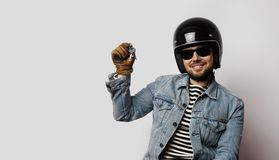 Young biker in a blue denim jacket pretending to ride a motorcycle isolated on white background.Man holding hand moto. Keys. Horizontal Royalty Free Stock Photos