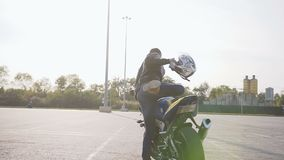 A young biker dressed in a black leather jacket, blue jeans with a helmet in his hands comes up with a motorcycle sits. On him and wears a helmet for safety stock video