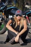 Young biker girl sitting in front of a motorcycle Royalty Free Stock Photo