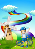 A young biker at the hilltop with a windmill and a rainbow Stock Photography