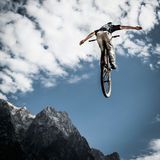 Young biker jumps handfree. With his bike in front of mountain Royalty Free Stock Photography