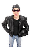 Young biker with leather jacket holding a helmet Royalty Free Stock Photos